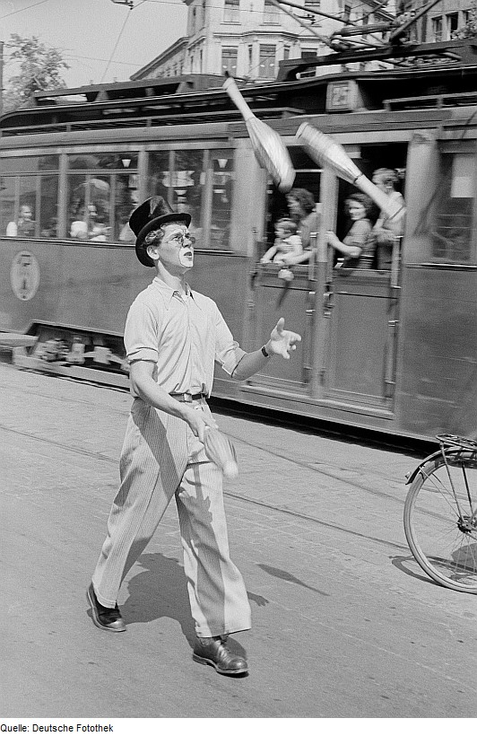 Vingtage photo of a juggler in top hat and partial clown-face walking past commuters on a streetcar traveling in the opposite direction.
