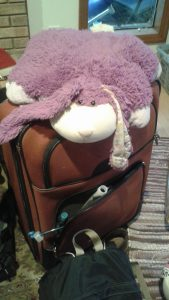 Large suitcase with rabbit pillow pet on top.