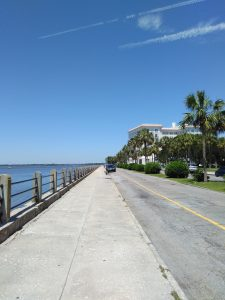 Concrete walk along The Battery, Charleston, SC, with house and palmetto trees.