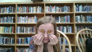 Girl with preztels covering her eyes, in front of bookshelf.